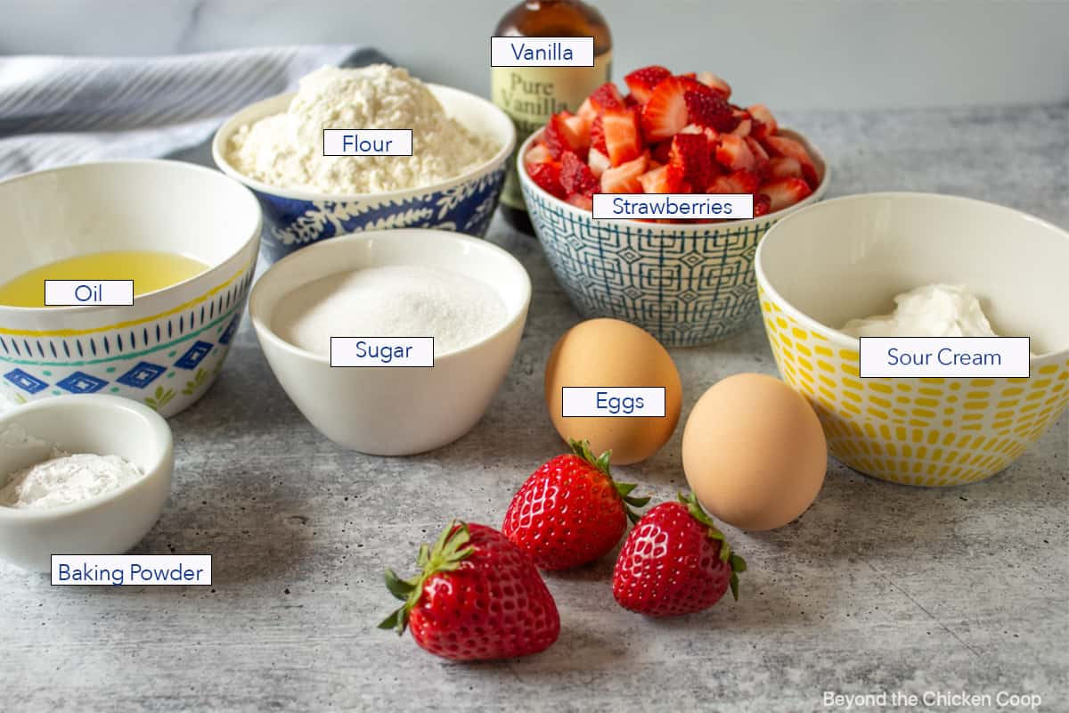 Fresh strawberries along with small bowls of ingredients for making muffins.