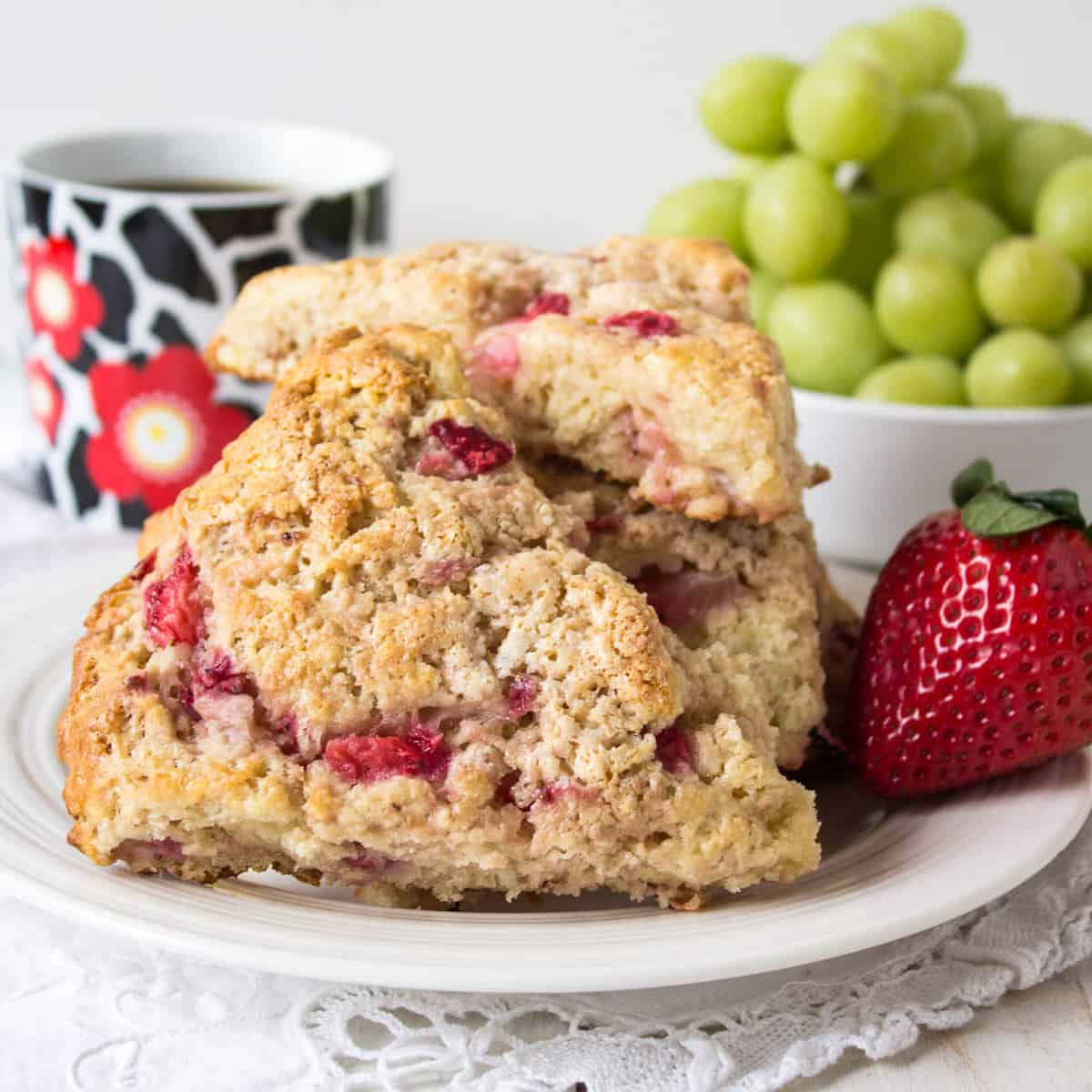 Two strawberry scones on a small white plate.