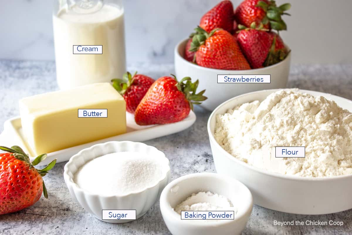 Small bowls filled with flour, sugar, flour and strawberries.