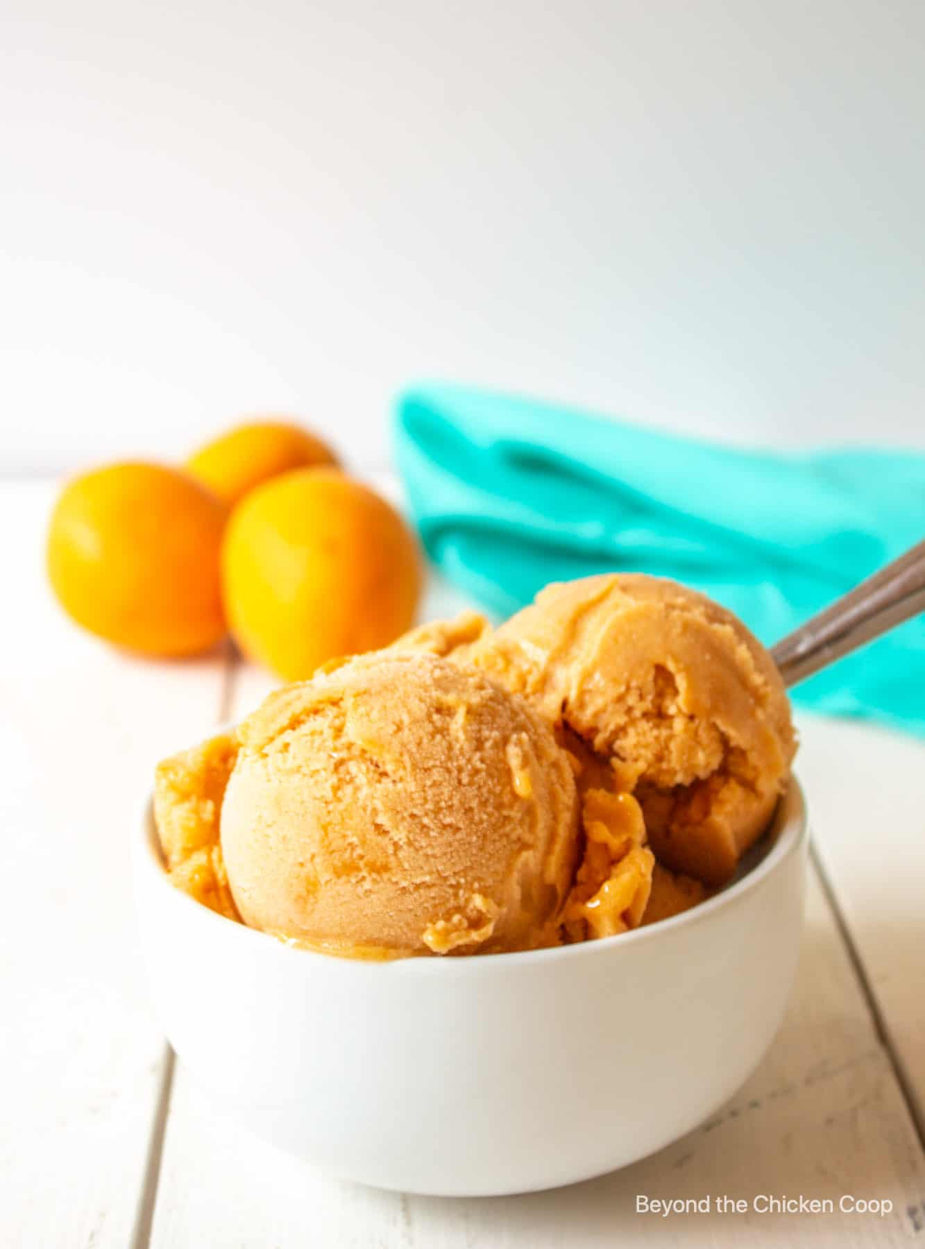 Scoops of apricot sorbet in a white bowl.