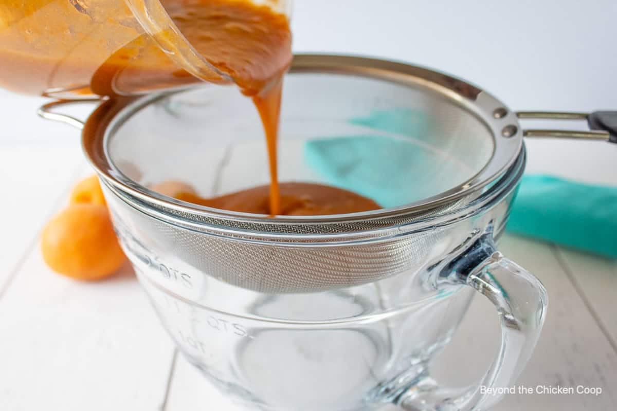 An apricot puree being poured through a sieve.