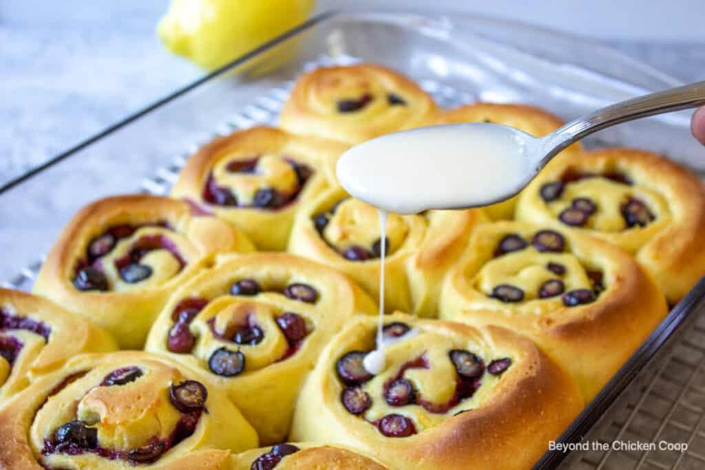 Adding a glaze to blueberry sweet rolls.