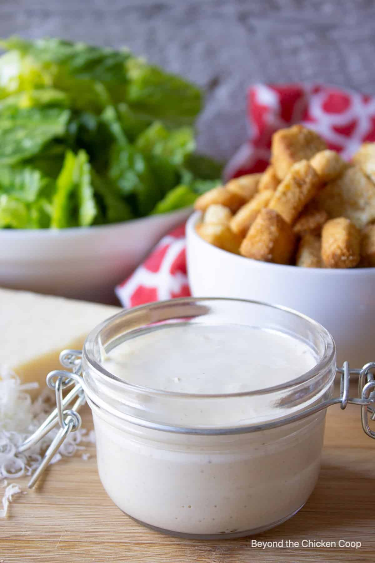 A jar filled with a creamy dressing with salad ingredients in the background