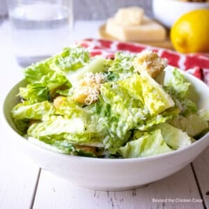 A white bowl filled with a Caesar salad.