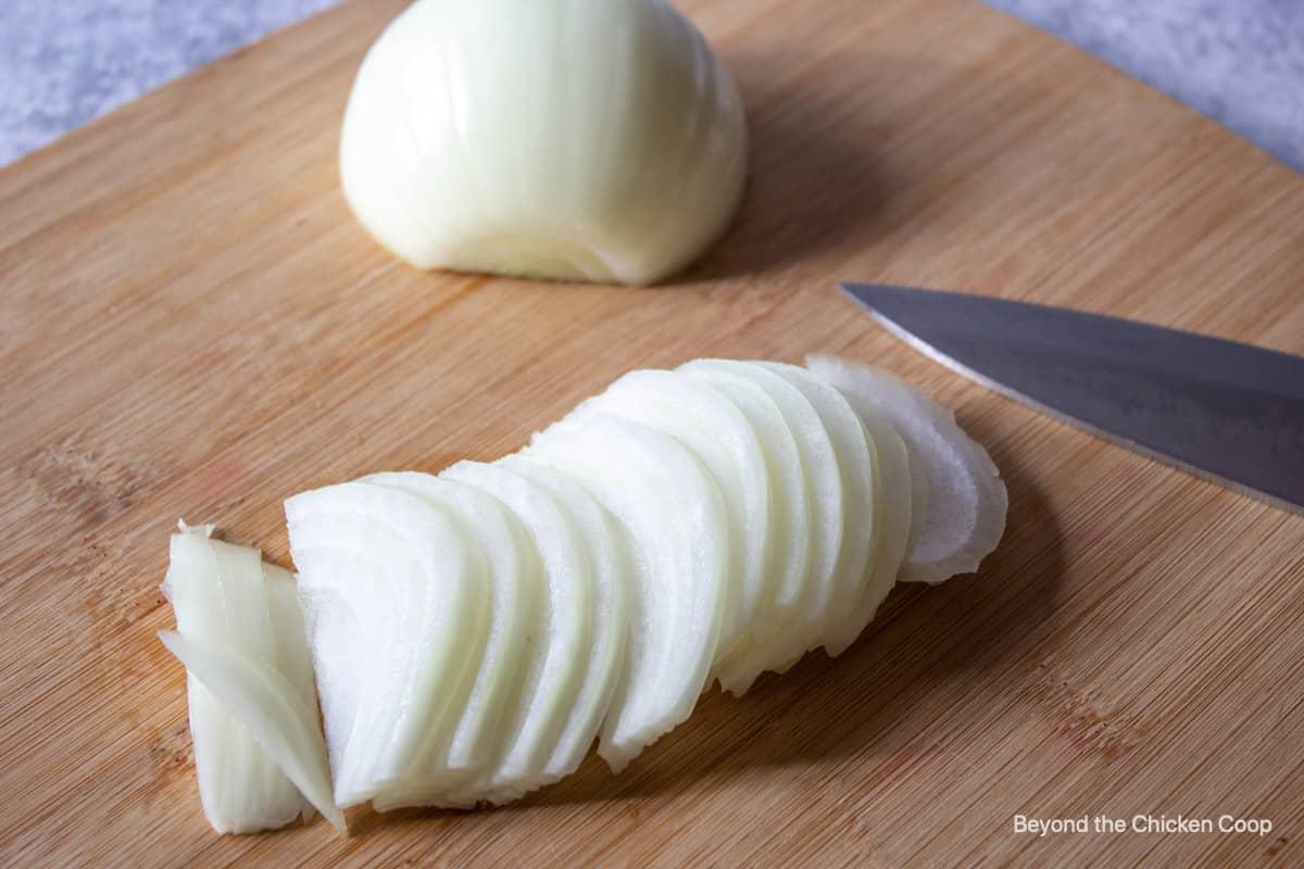 Sliced onions on a cutting board.