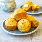 A pile of cornbread muffins on a blue plate.