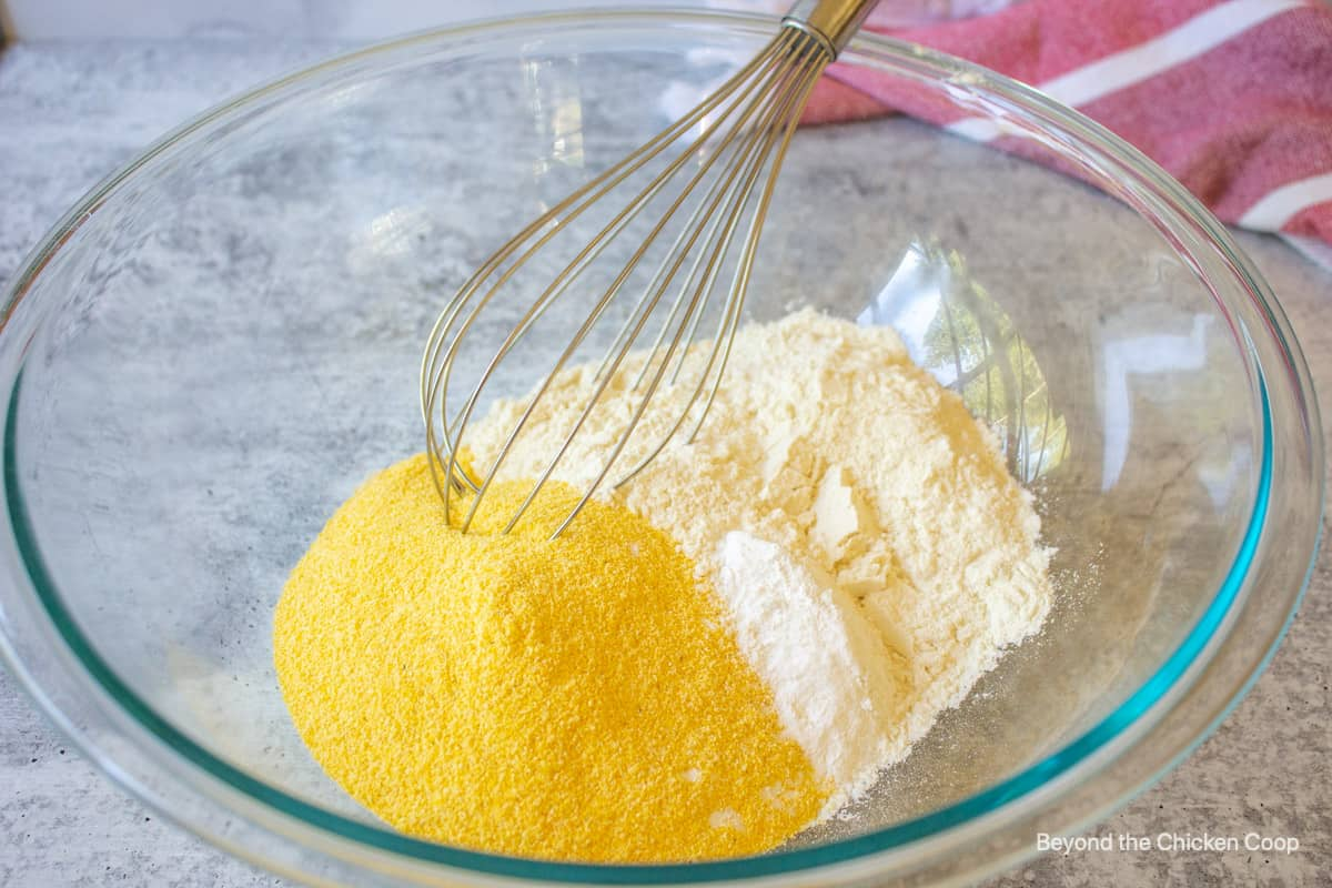 A glass bowl with cornmeal and flour.