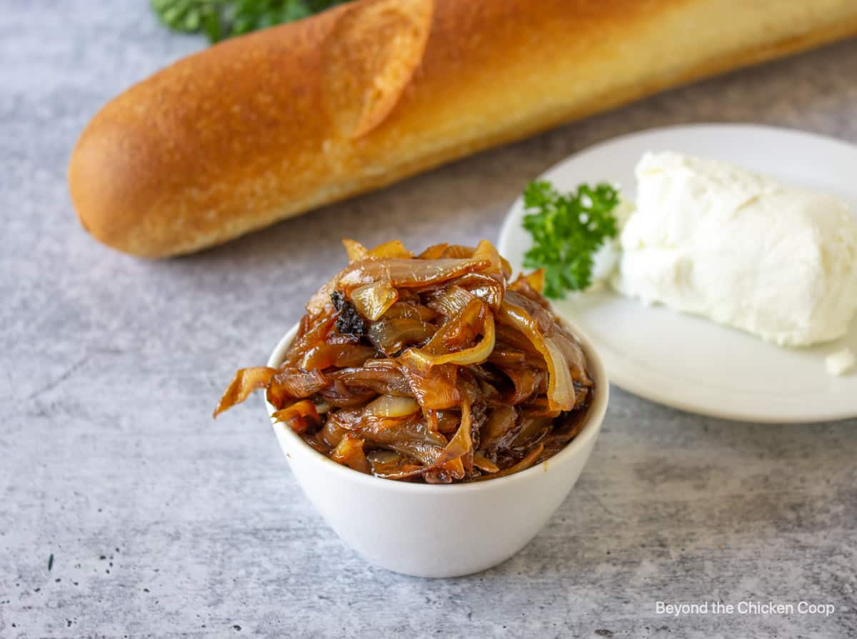 Caramelized onions in a small bowl next to a log of goat cheese and a loaf of bread.