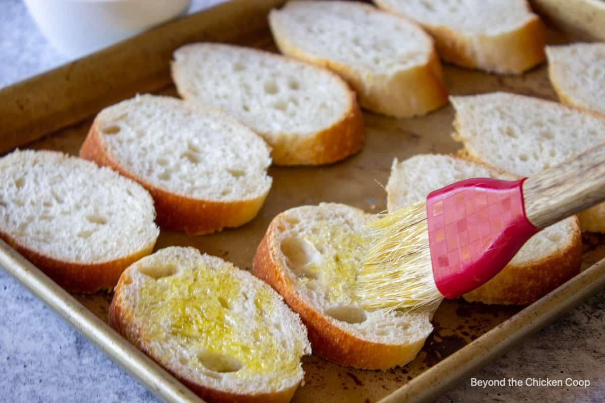Brushing olive oil onto sliced bread.
