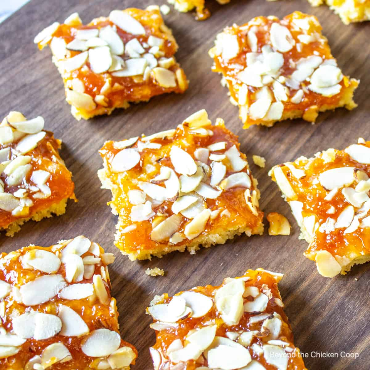 Apricot bars topped with slice almonds on a wooden board.