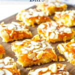 Squares of apricot bars with almonds on a wooden board.