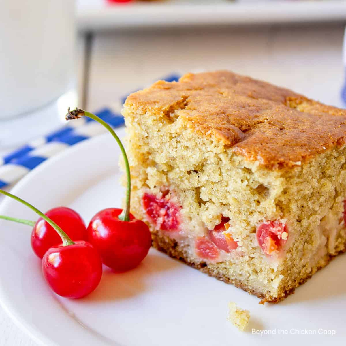 A square piece of cake filled with cherries.