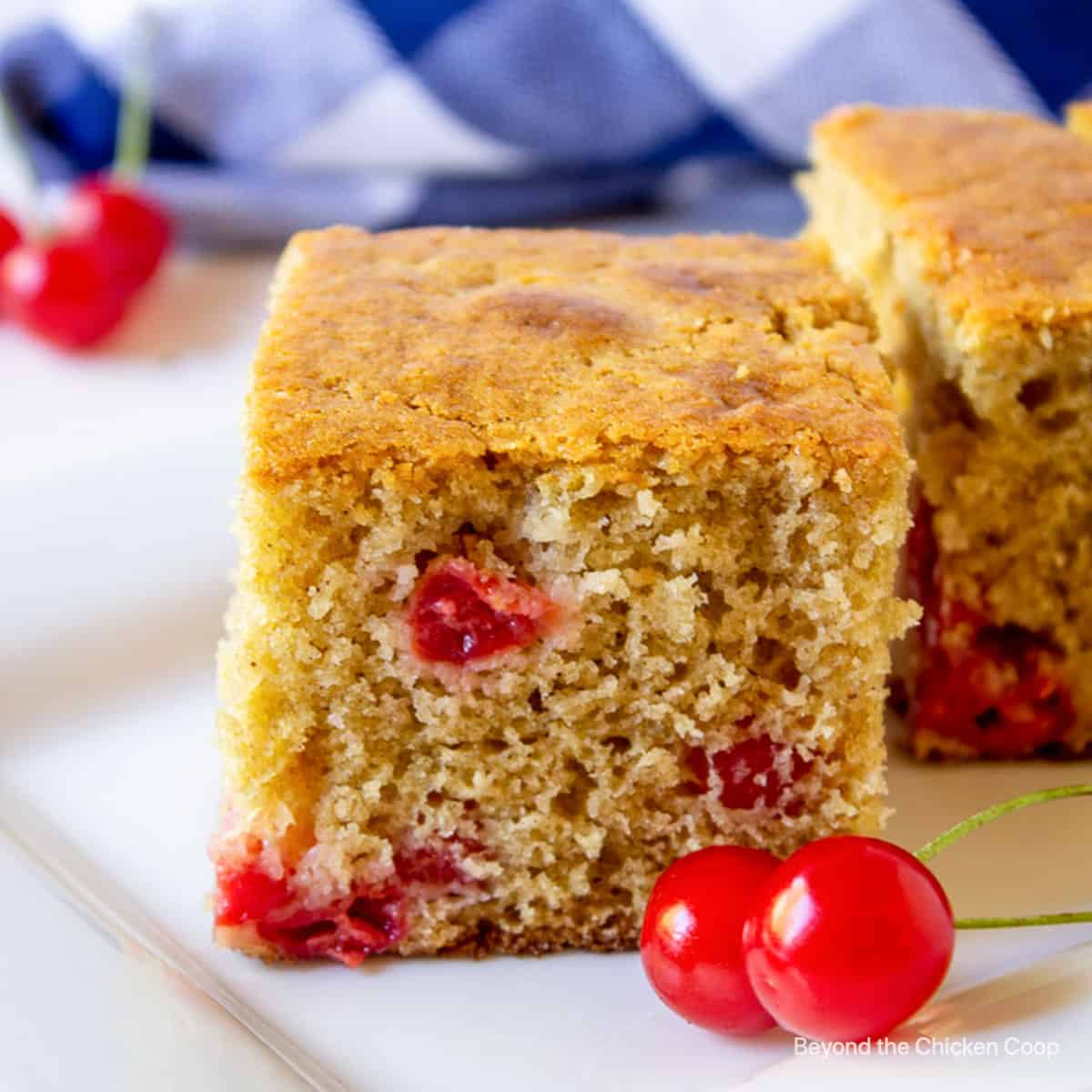 A slice of cherry cake on a white platter.