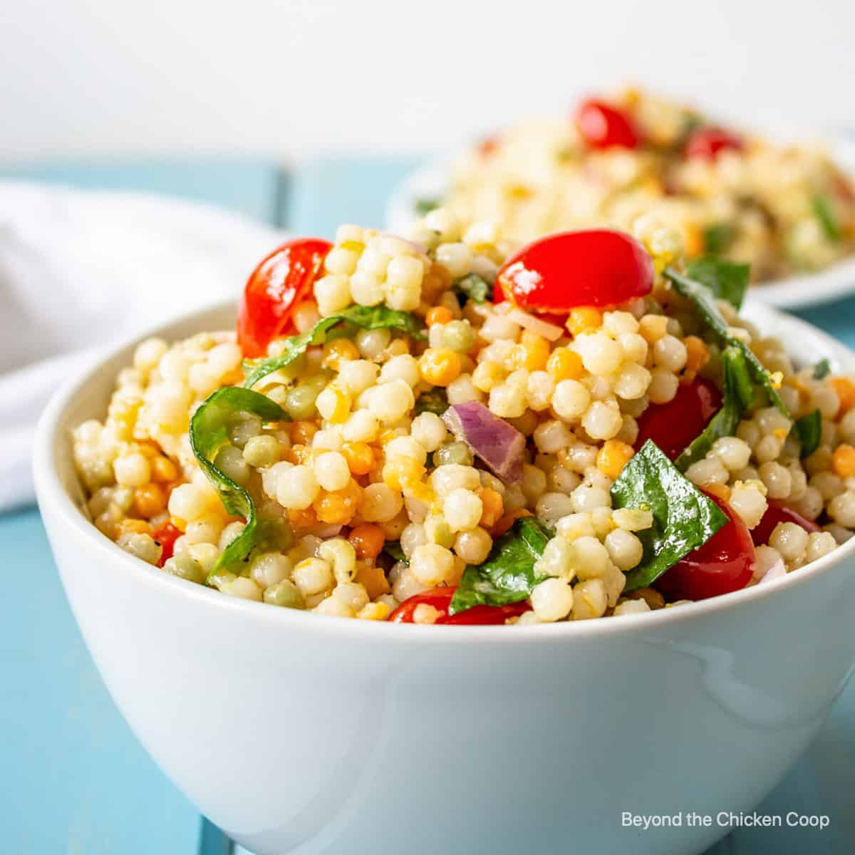 A couscous salad with tomatoes and spinach.