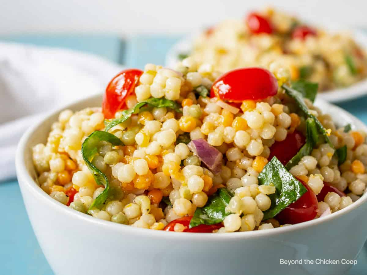 A couscous salad with tomatoes and spinach in a white bowl.