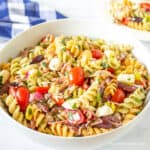 A bowl filled with fussili pasta, tomatoes and cheese.