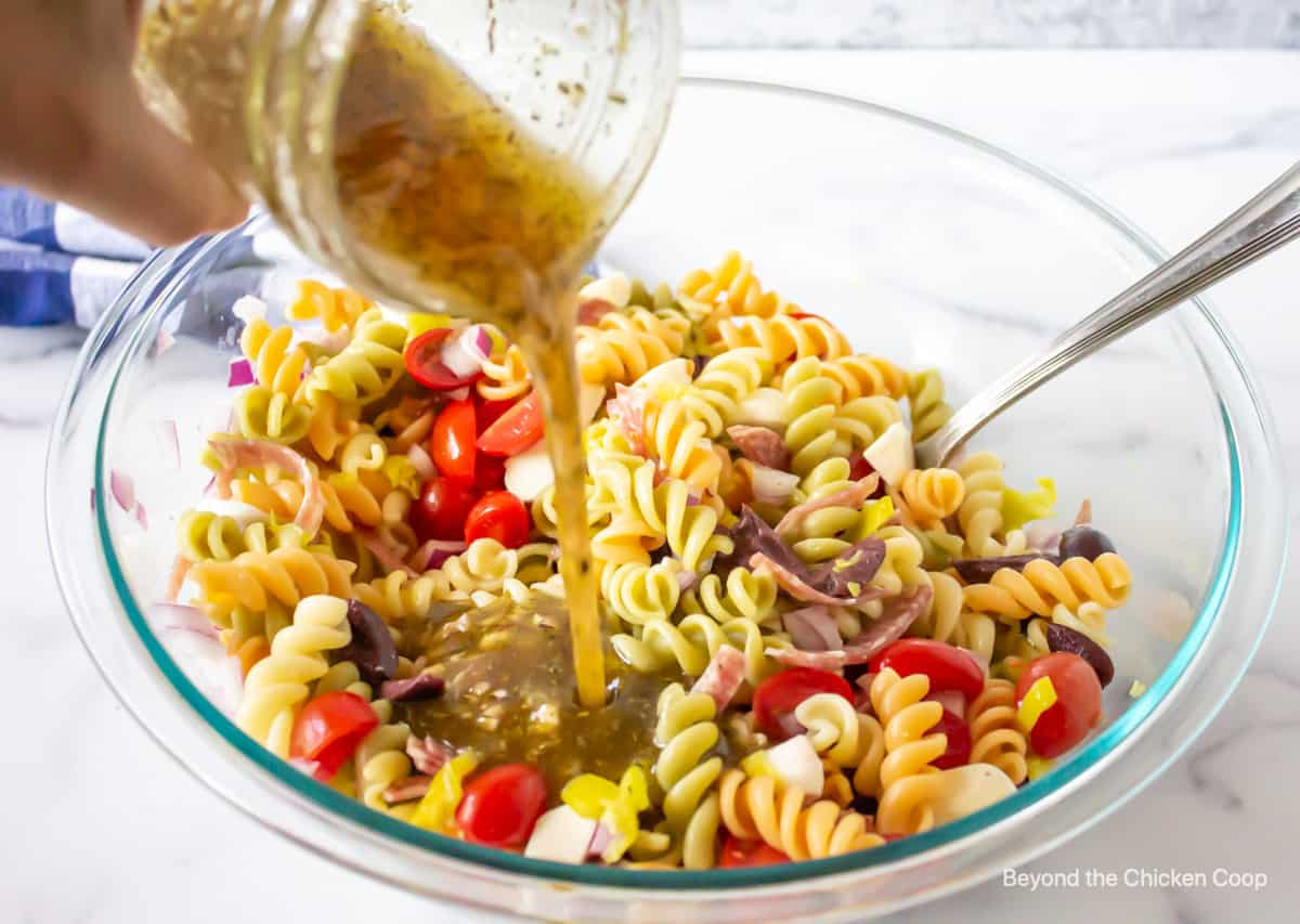 An Italian dressing being poured over a pasta salad.
