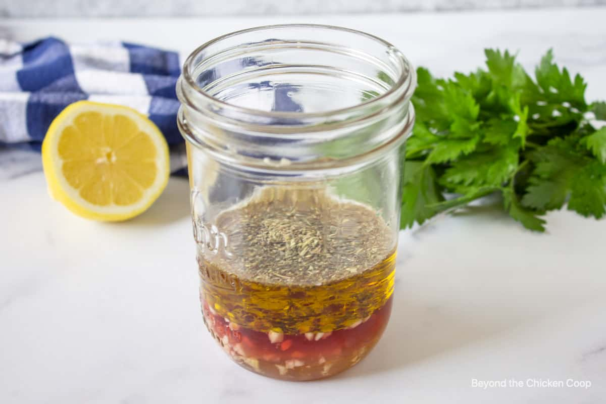 A glass jar filled with olive oil, vinegar and herbs.