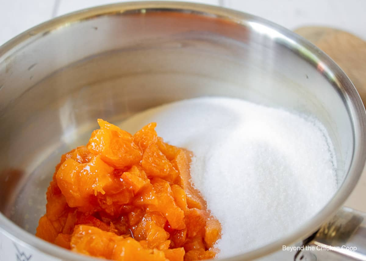 A pot with sugar and cut apricots.