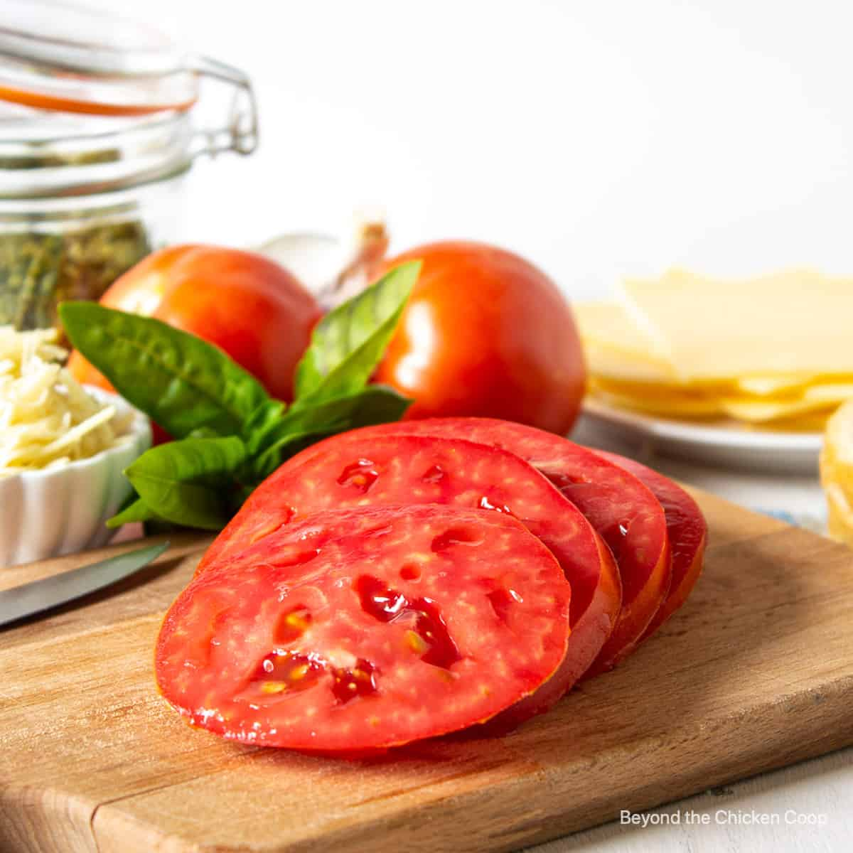 Sliced tomatoes on a wooden board.