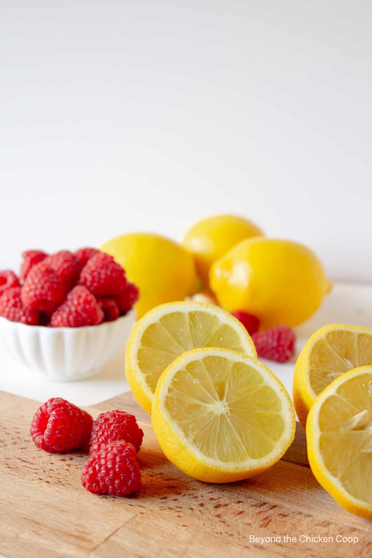 Fresh lemons and raspberries on a wooden board.