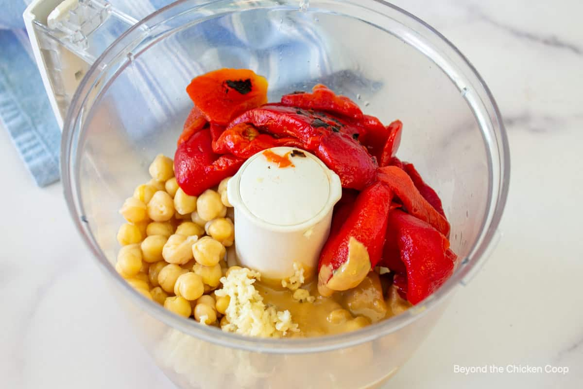 Chickpeas, bell peppers and tahini in a food processor bowl.