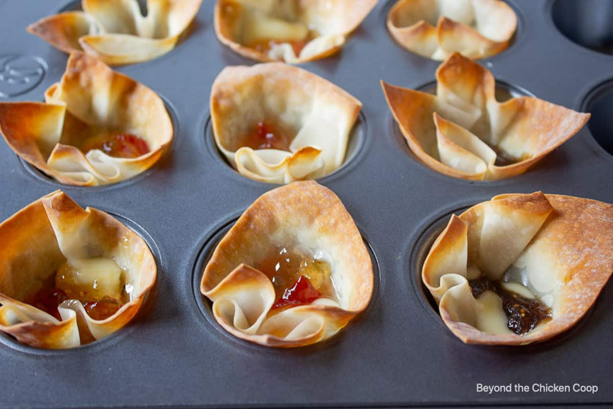 Wonton cups filled with baked cheese and jelly.