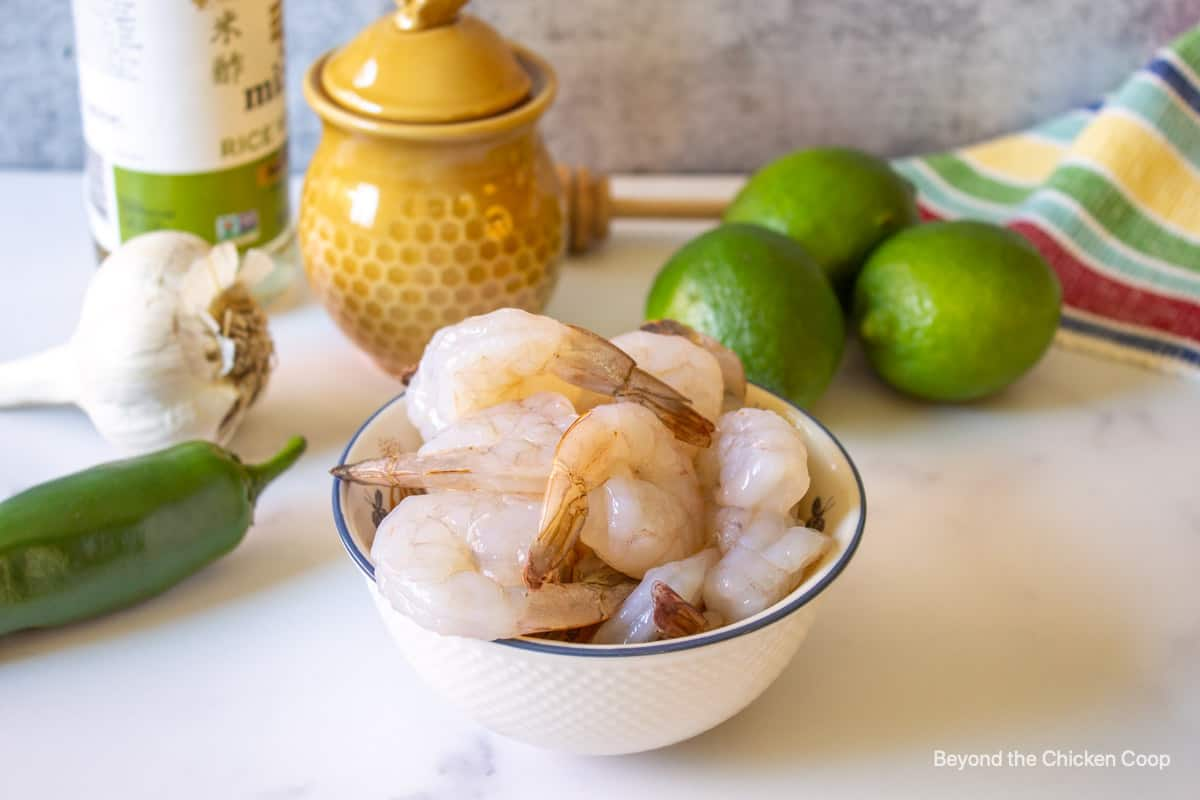 A bowl with shrimp next to fresh limes.