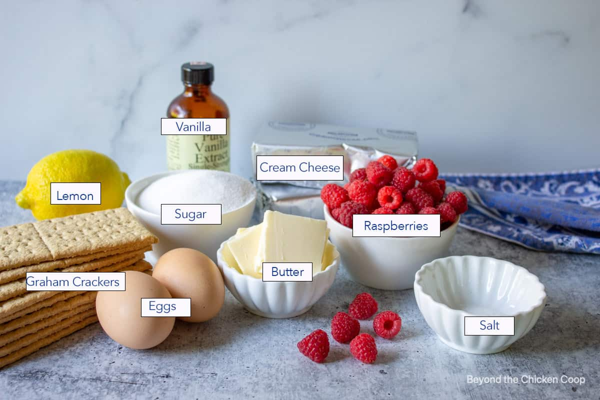 Ingredients for making cheesecake bars with raspberries.