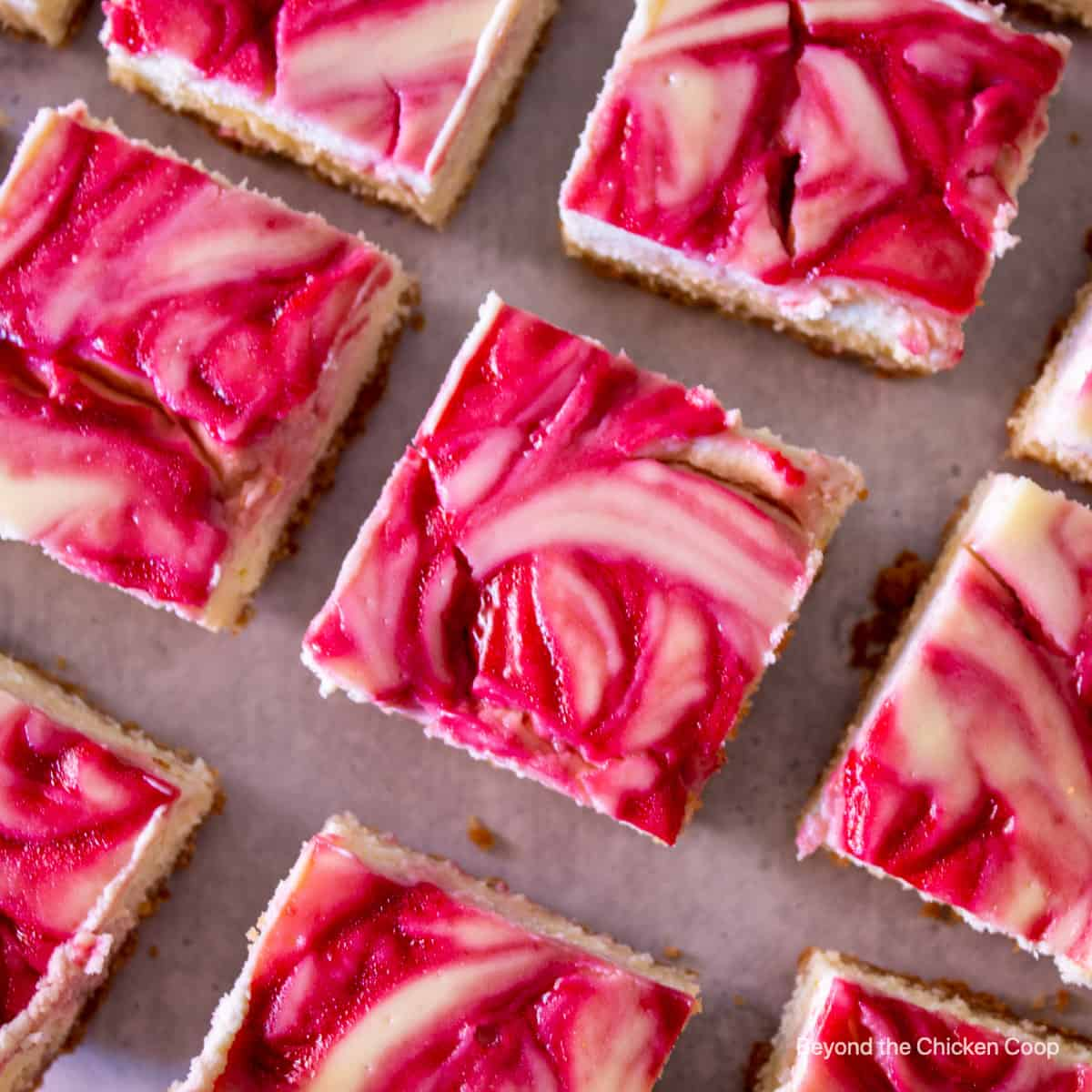 Cheesecake squares topped with a raspberry swirl.