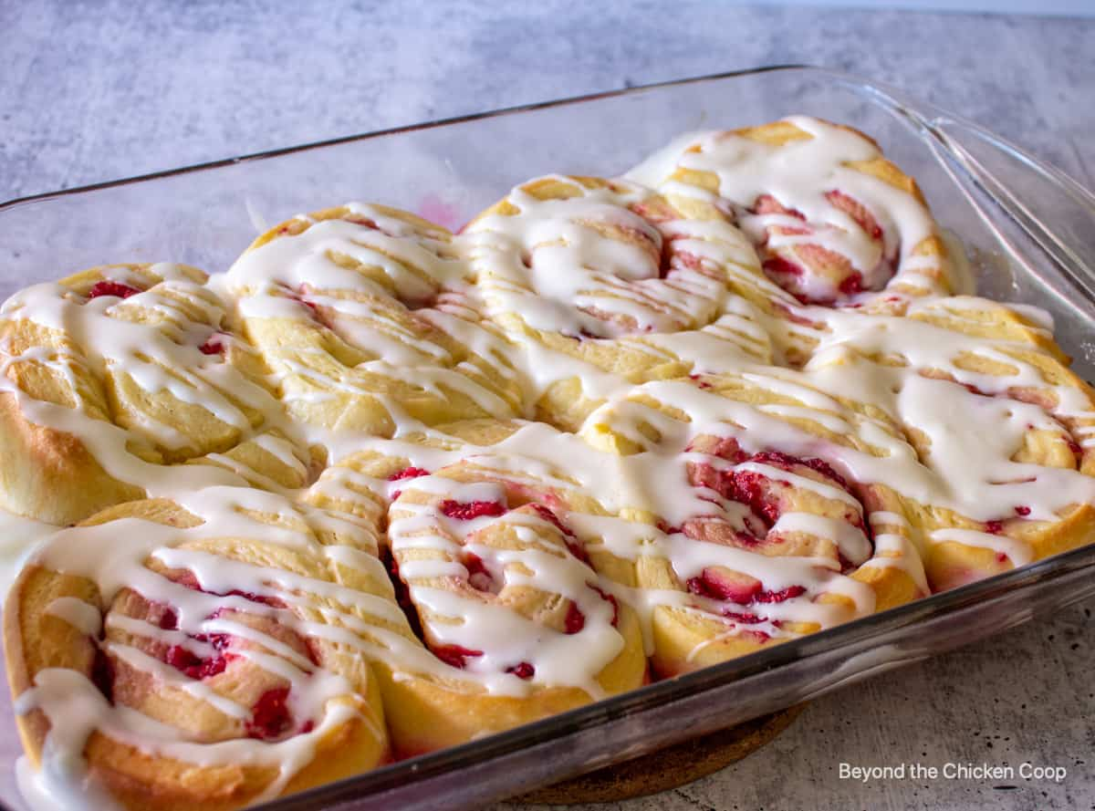 Raspberry sweet rolls topped with a glaze in a glass baking dish.