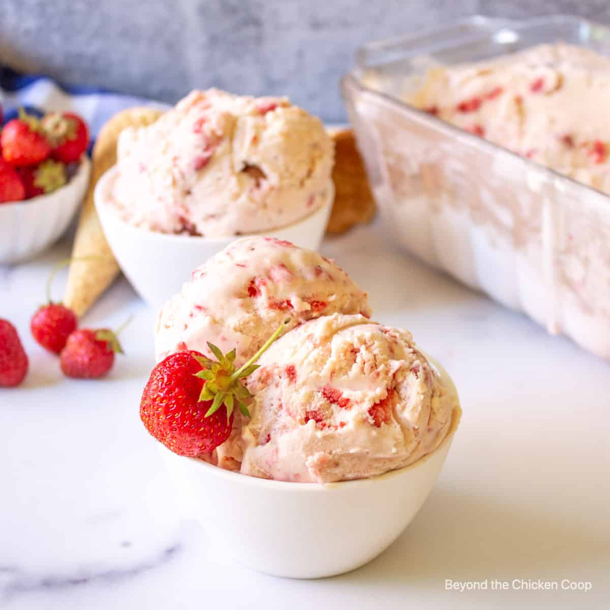 Scoops of strawberry ice cream in a bowl.