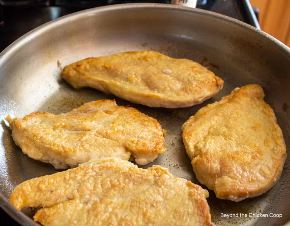 Browned chicken breasts in a pan.