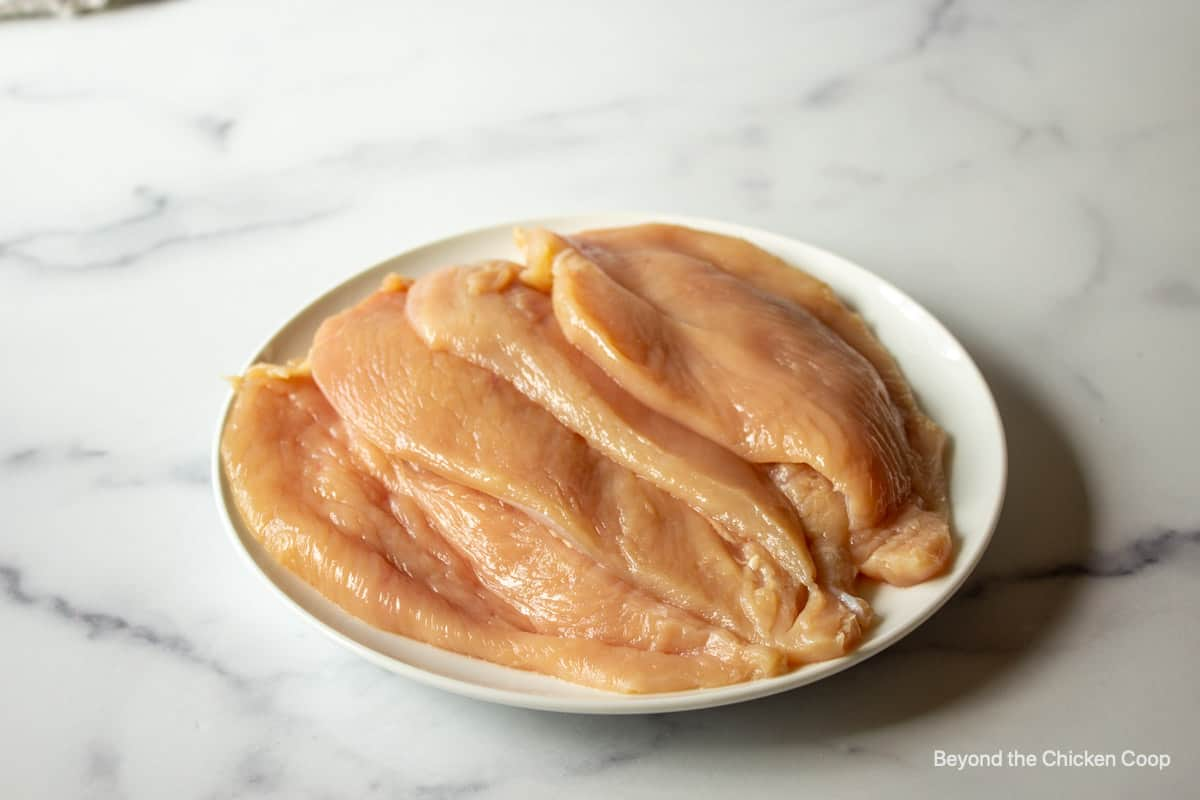 Four chicken breasts on a plate.