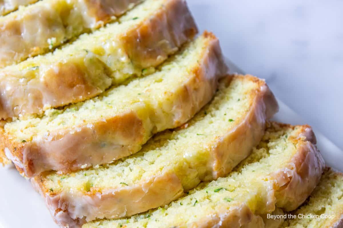 Sliced zucchini bread with a glaze.