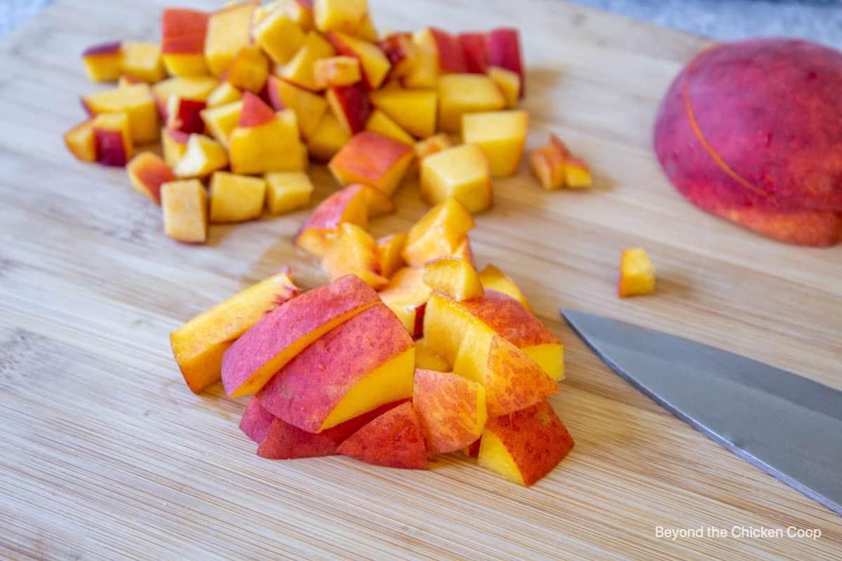 Diced peaches on a cutting board.