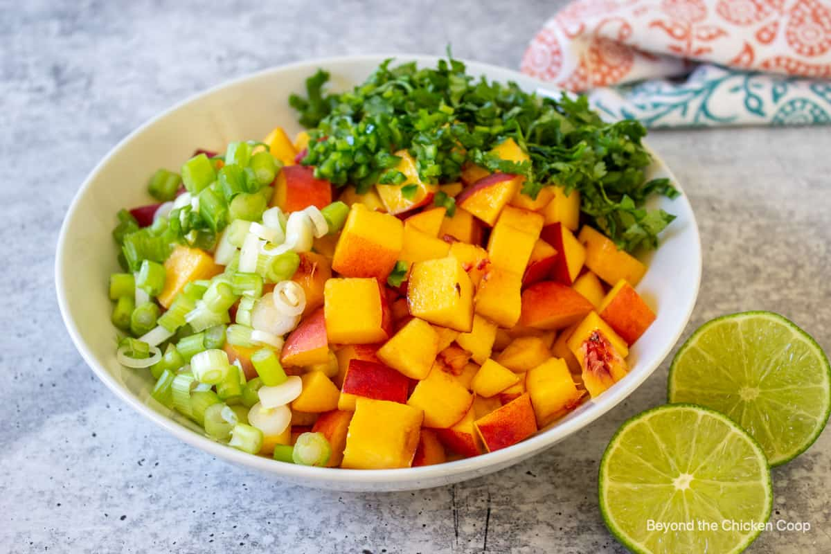 Chopped peaches and cilantro in a bowl.