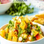 A bowl of fresh peaches dices with cilantro and onions.
