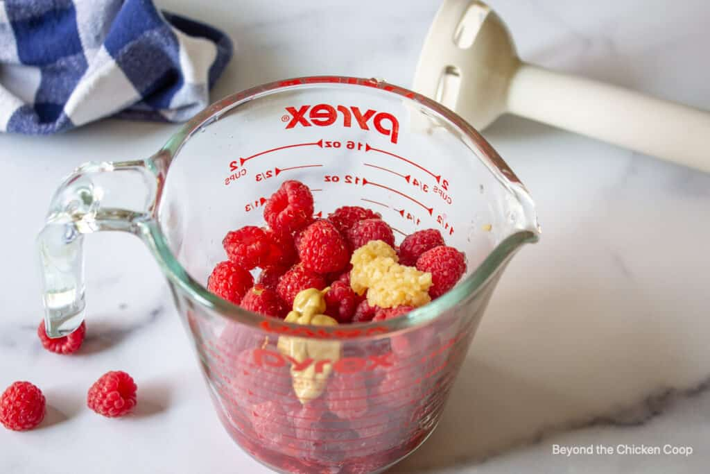 Raspberries, garlic and dijon mustard in a glass measuring jar.