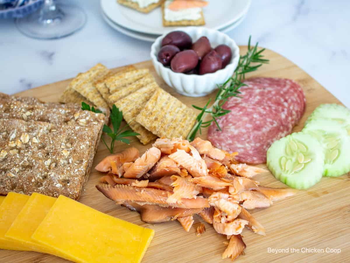 Smoked fish on a wooden board with cheese and crackers.