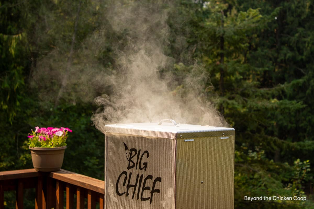 Smoke coming out of the top of a smoker.