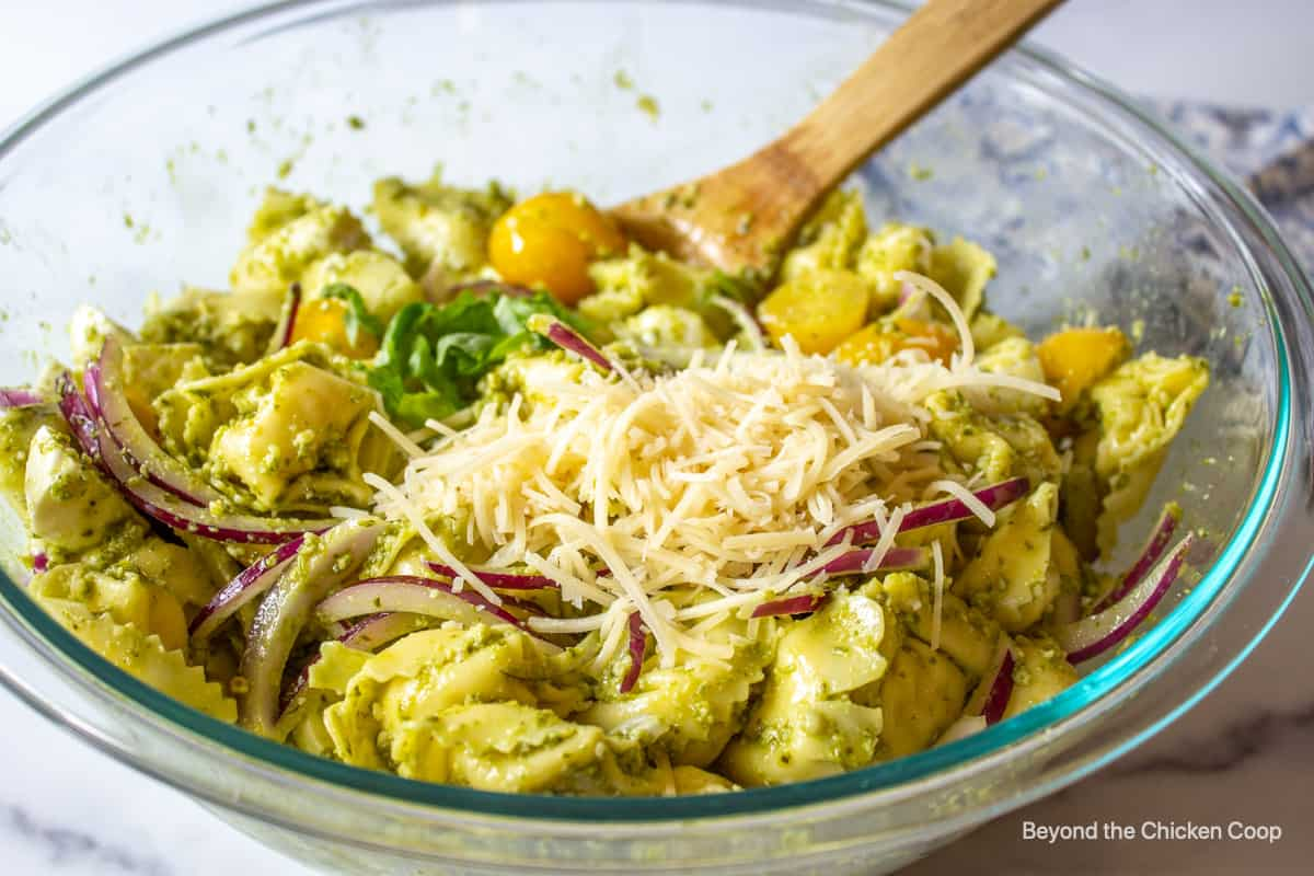 Parmesan and fresh basil on a pesto tortellini salad.