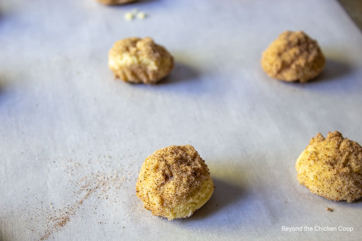 Cookie dough balls with cinnamon and sugar on a baking sheet.