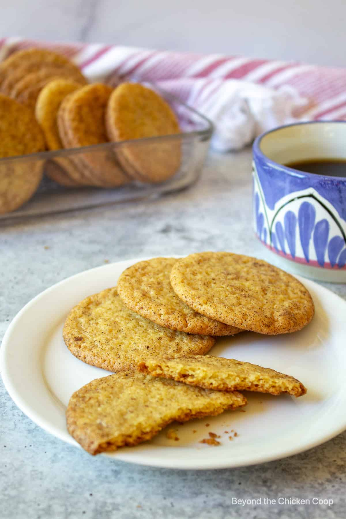 Cookies on a white plate with a cup of coffee in the background.