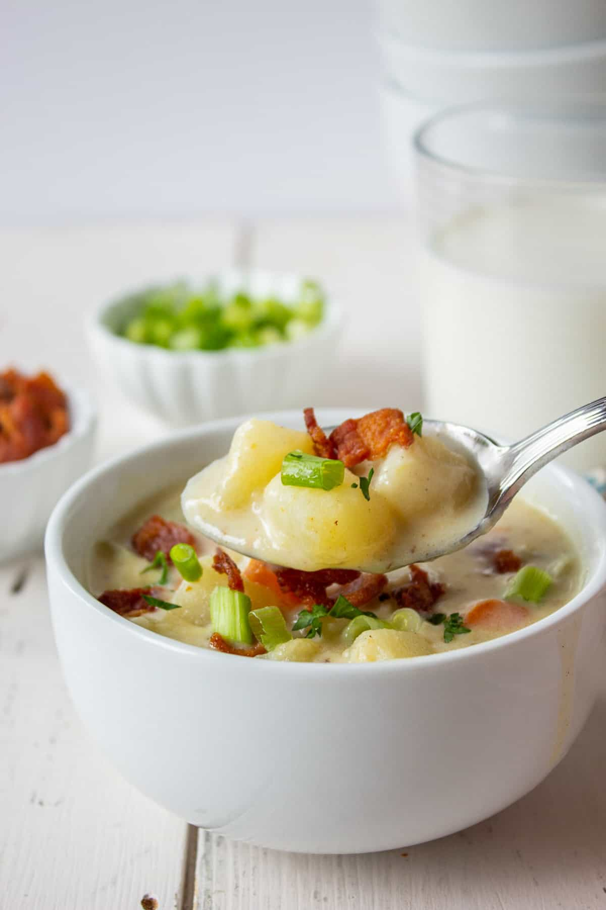 A spoonful of potato soup over a bowl filled with soup.