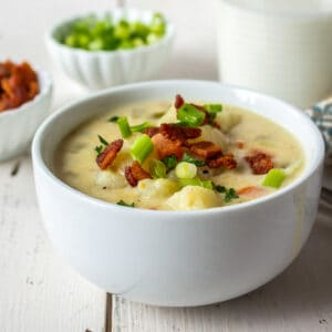 A white bowl filled with a potato soup topped with bacon.