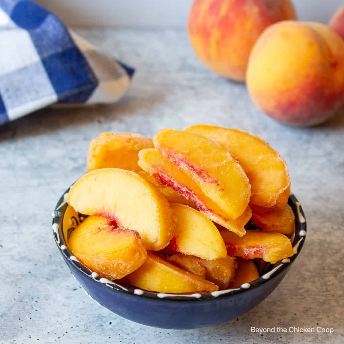 A bowl with frozen sliced peaches.