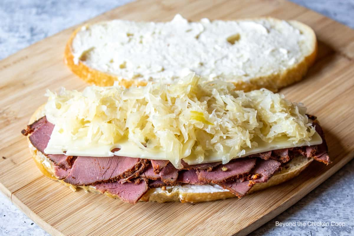 Making a sandwich with pastrami, cheese and sauerkraut.