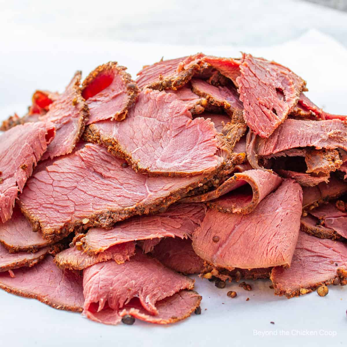 Slices of homemade pastrami on butcher paper.