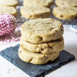 Three pecan cookies stacked on a black coaster.